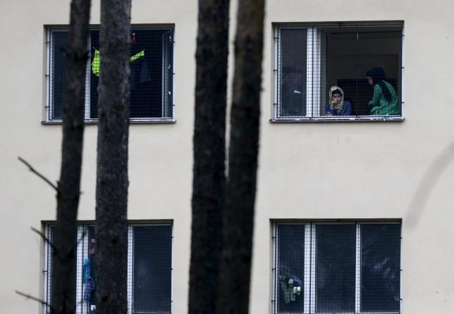 Migrants look out of a window in the Facility For Detention Of Foreigners in Bela-Jezova