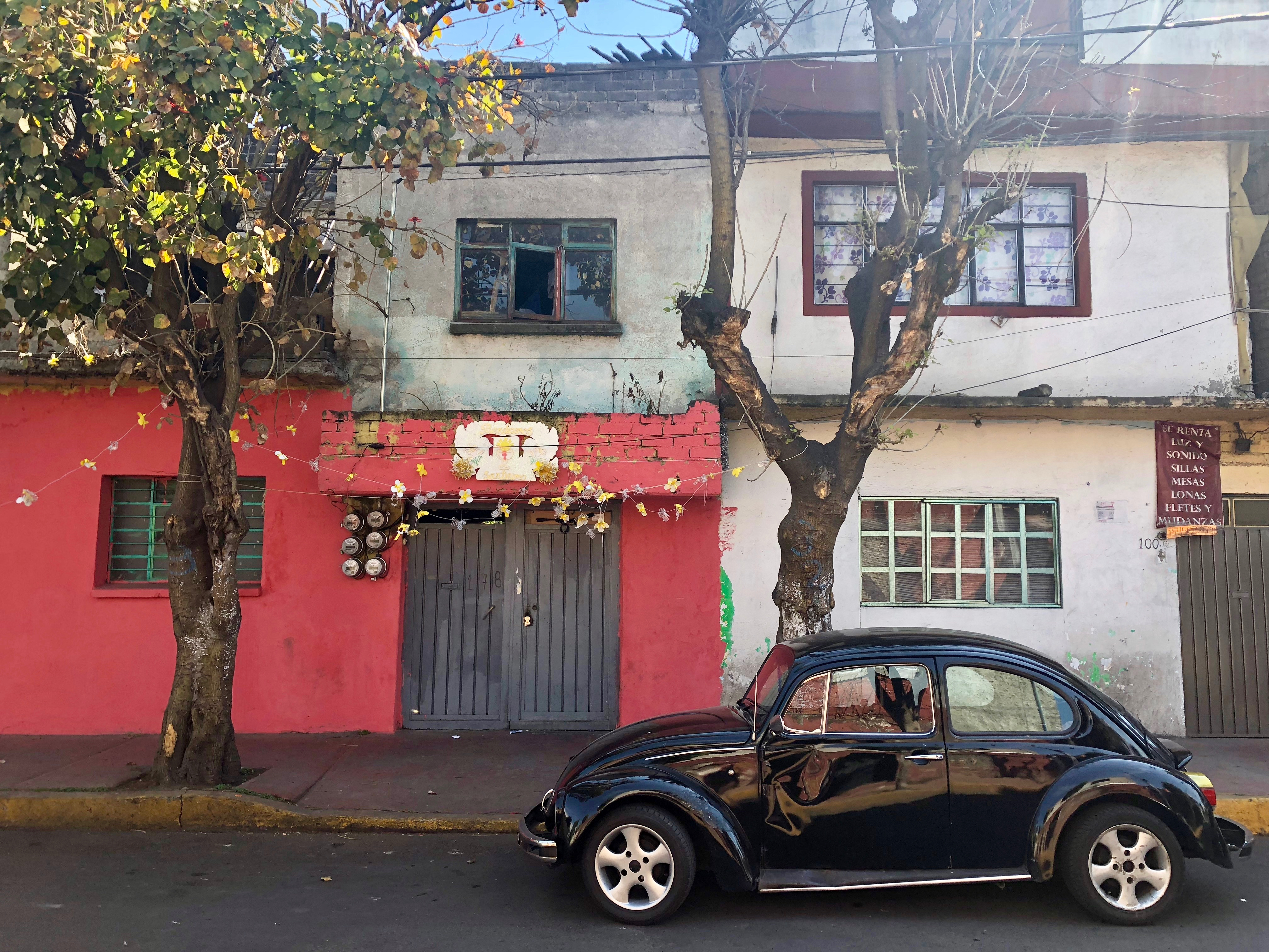 A beaten-up black Volkswagen Beetle is parked along a residential street in Xochimilco, Mexico City, Feb. 2, 2019.